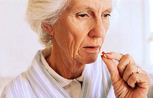 Пожилая женщина с таблеткой